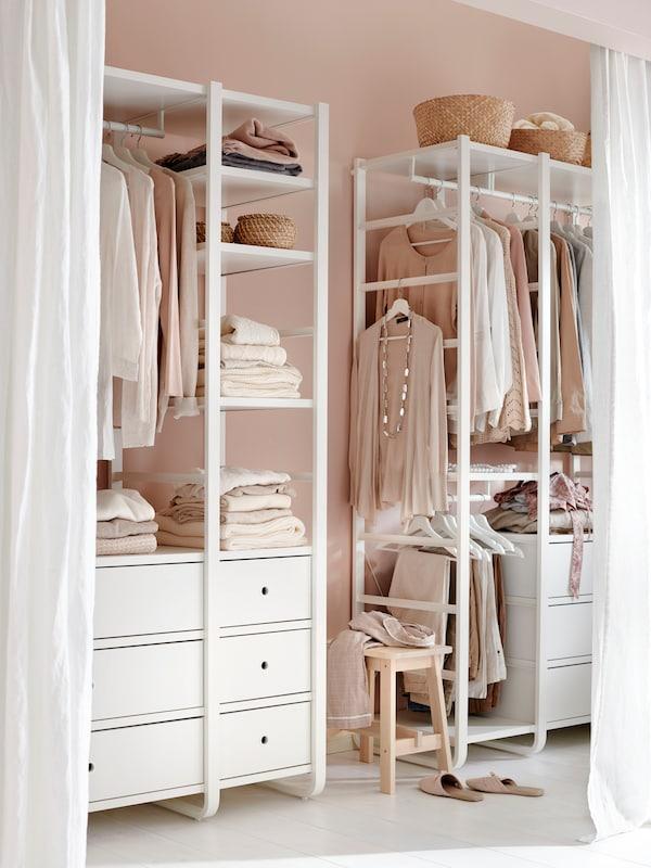 XCONTENT Stanza grigio pallido con toeletta bianca, sedia imbottita grigia e guardaroba bianchi con illuminazioni per mobili in alto.