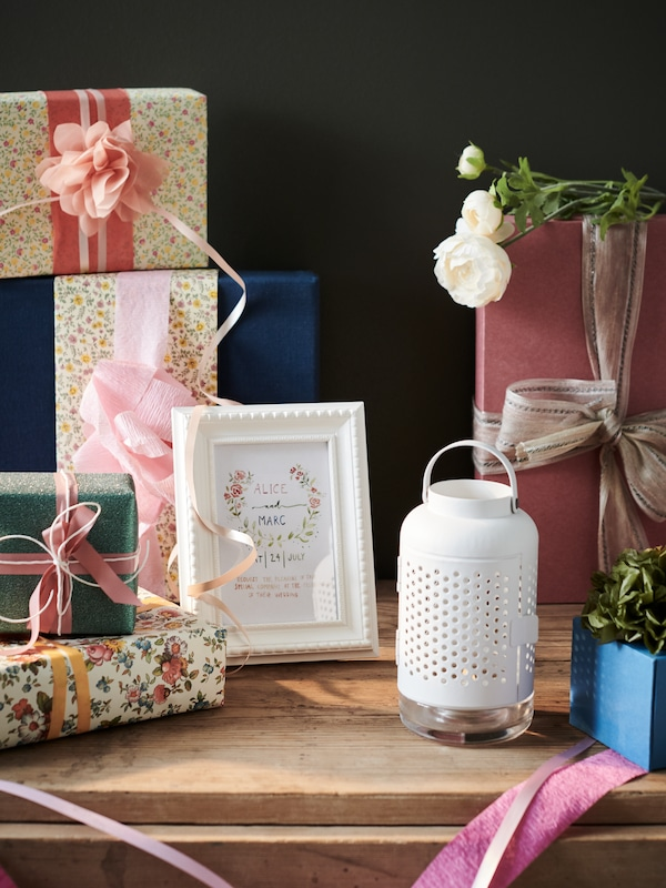 Wooden table laden with wrapped gifts and decorated with an ÄDELHET tealight lantern and a card in a white HIMMELSBY frame.