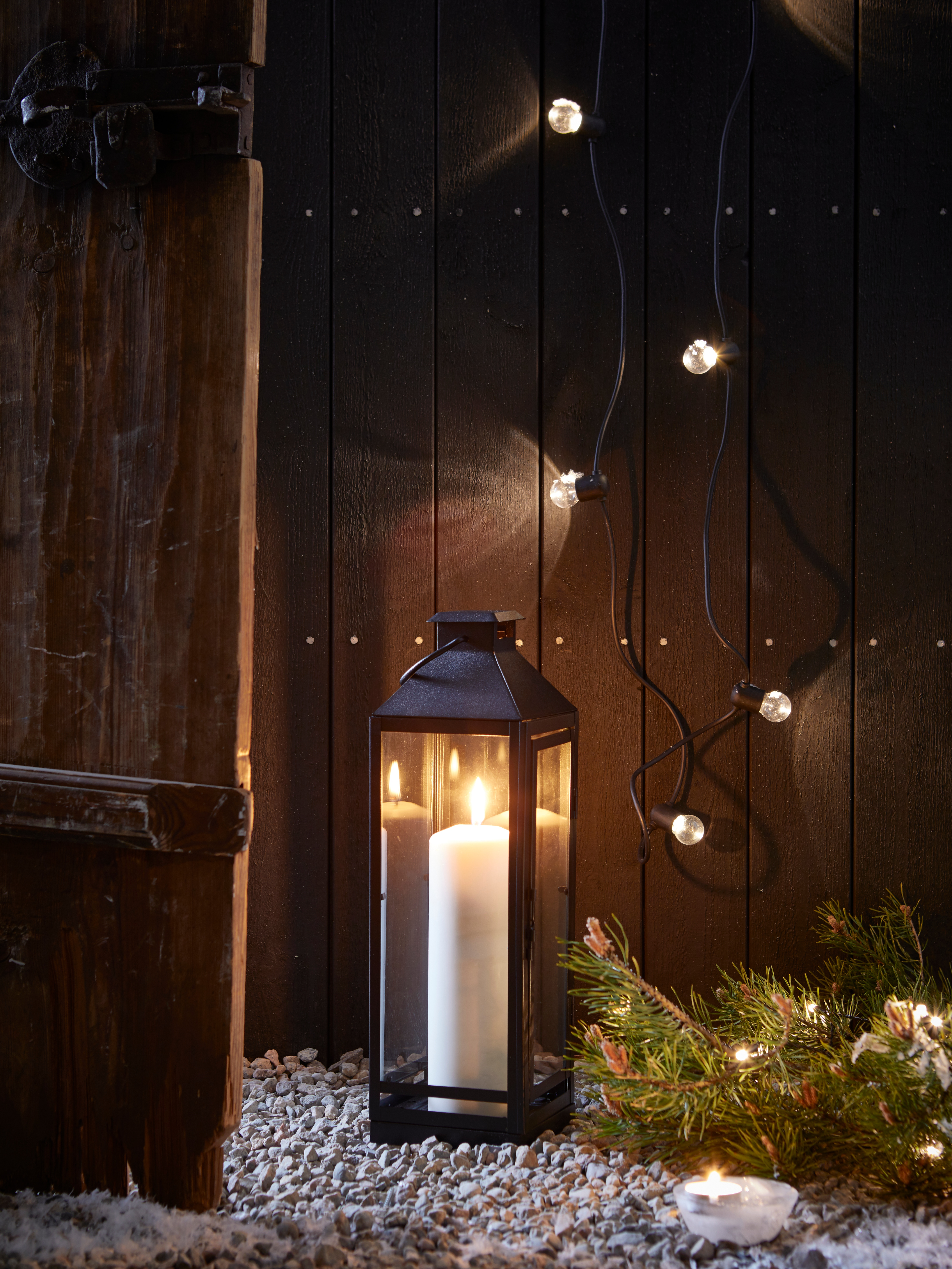 LEDLJUS fairy lights on a wooden fence, with a candle in a black lantern on gravel, a tealight and an evergreen branch.