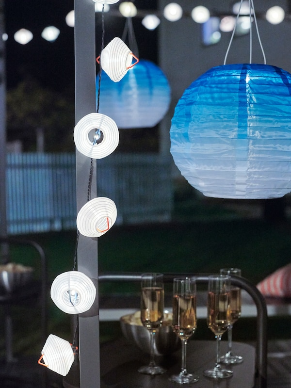 Blue-toned solar-powered SOLVINDEN LED pendant lamps, white lighting chains, wine glasses and snacks in a garden at night.