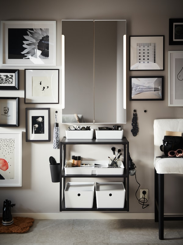 A white STORJORM mirror cabinet with built-in lighting on a wall with framed pictures and an anthracite shelving unit.