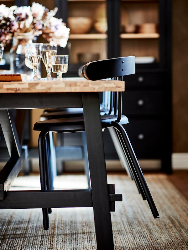 Zwarte YNGVAR stoelen opgehangen aan de armleuningen op het tafelblad van een SKOGSTA eettafel, met daaronder een juten vloerkleed.