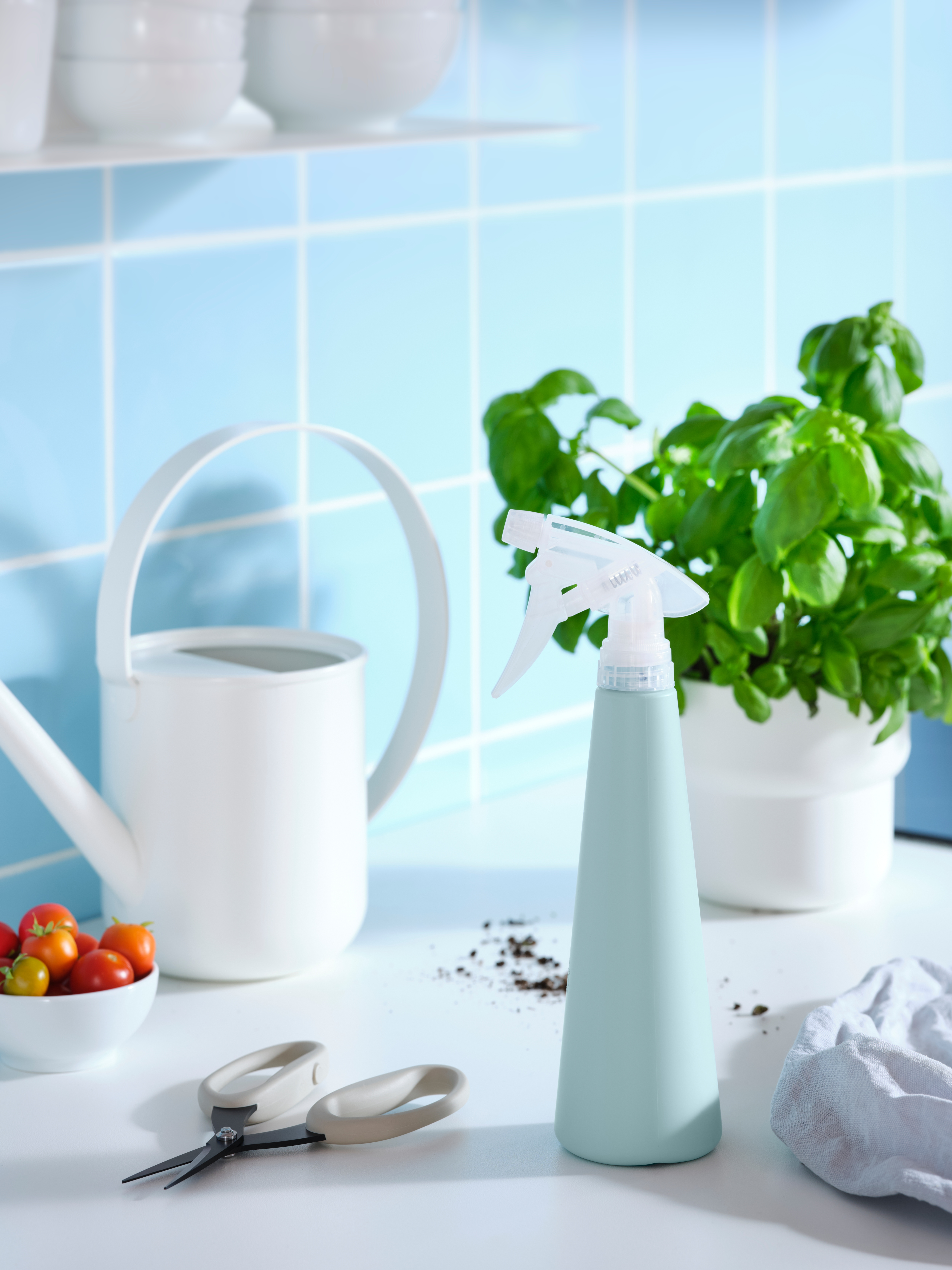 A kitchen top with a watering can, a TOMAT spray bottle, a pair of JACKFRUKT herb scissors, basil and a bowl of tomatoes.