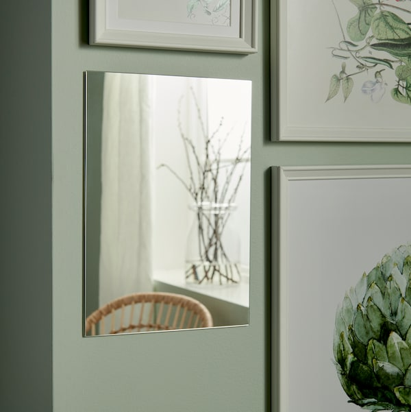 A mirror on a light green wall among a number of various pictures with picture frames.