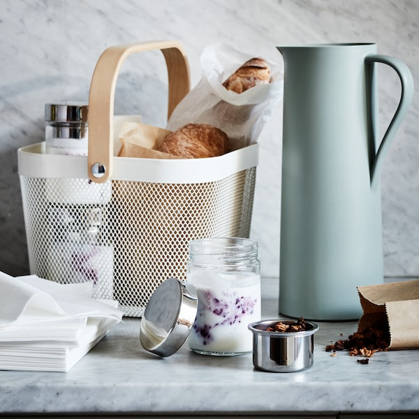 Countertop with white RISATORP basket with bread inside, beside a blue pitcher and an open jar with yogurt and jam.