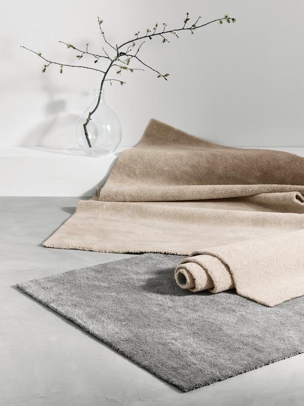 Tapete de pelo curto STOENSE em cinzento no chão junta a uma jarra, com dois tapetes STOENSE em branco-bege em cima, um enrolado e o outro meio desenrolado.
