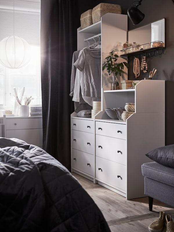 En hvid HAUGA opbevaringskombination står op ad en væg i et soveværelse over for en grå HAUGA polstret seng.
