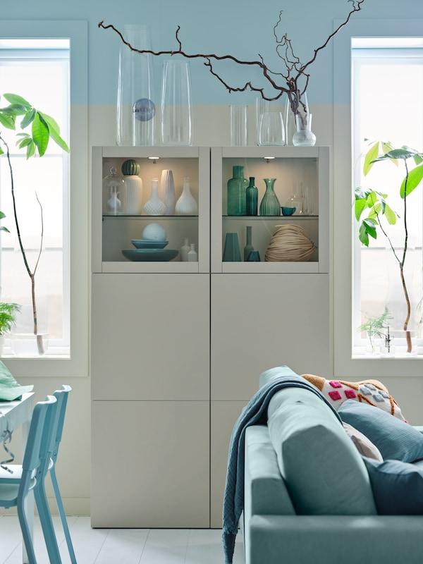 Svijetla prostorija s VIMLE sofom na razvlačenje i BESTÅ kombinacijom za odlaganje sa staklenim vratima.
