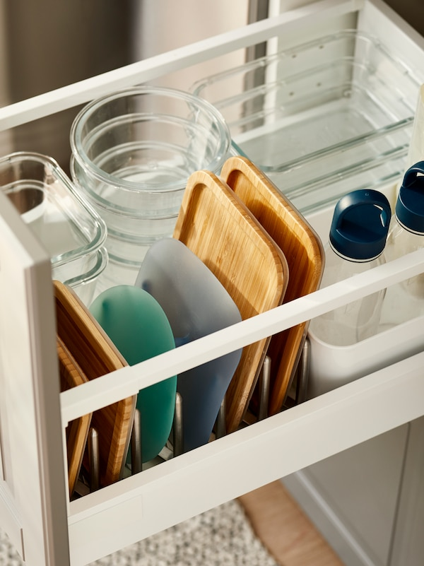 Kitchen drawer with stacks of glass lunch boxes in different sizes, and respective lids on file in a pot lid organizer.