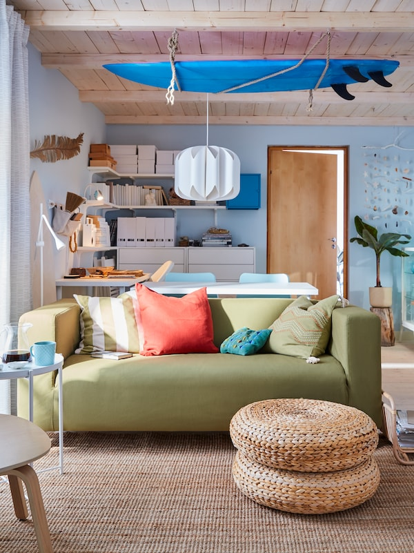 A surf-inspired living room with a yellow-green sofa, blue surfboard on the ceiling, white shelves, and blue walls.