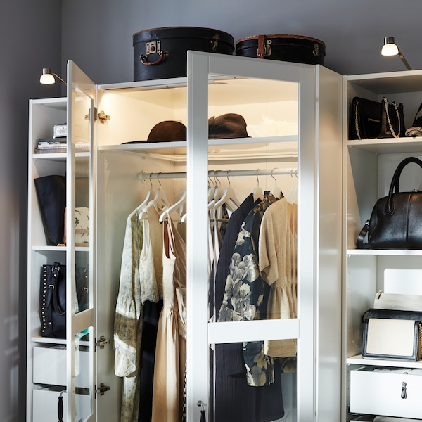 A room with a PAX wardrobe with two open glass doors and various compartments holding clothes and accessories.