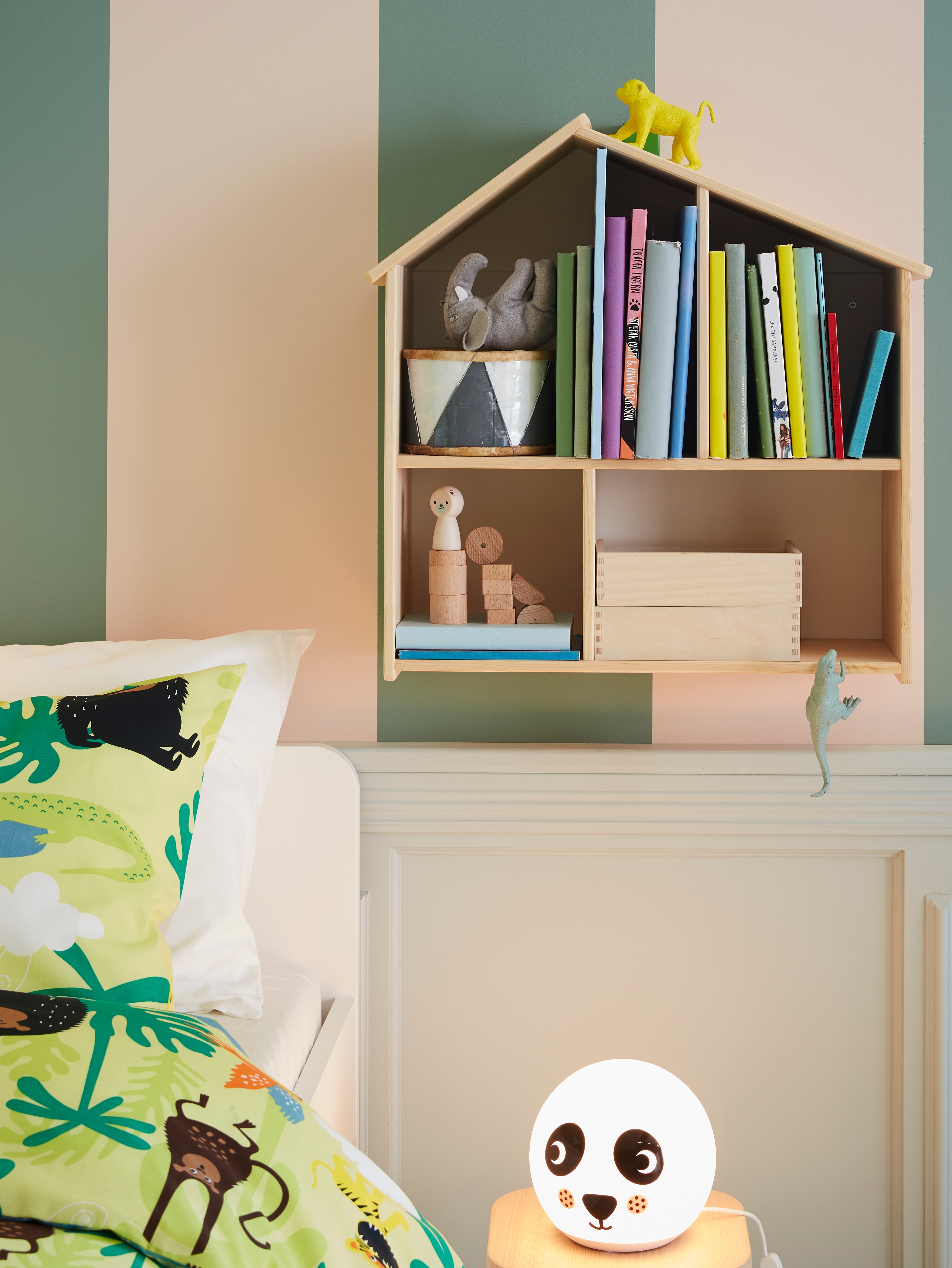 Children's bedroom with colourful bed linens, panda LED table lamp and wooden wall shelf in shape of a doll house.