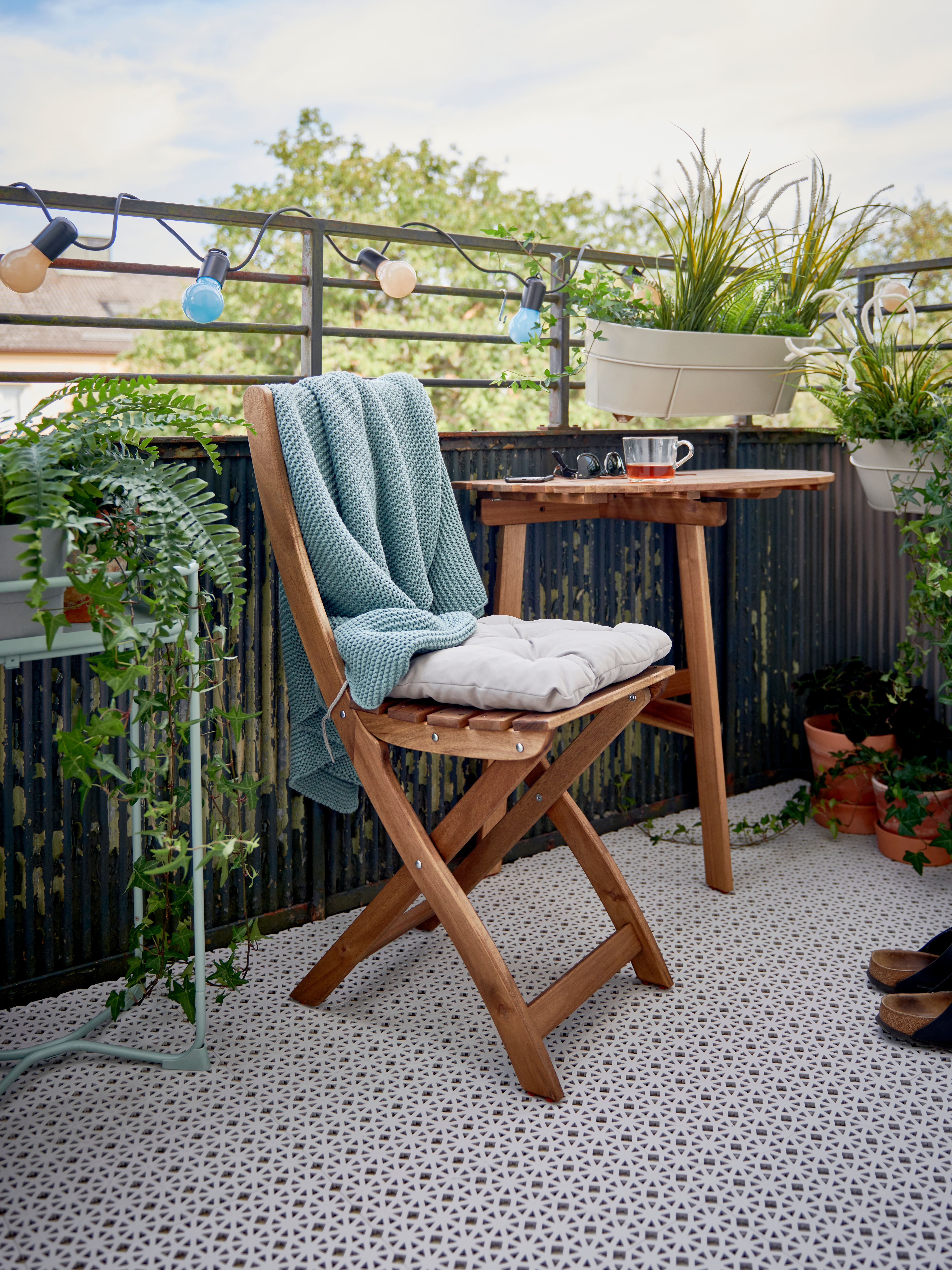 A balcony prepped for spring with light grey ALTAPPEN floor decking, plants, a colourful light chain, table and chair.