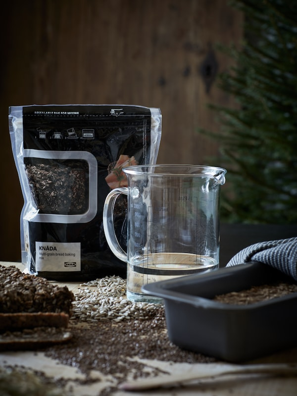A worktop with KNÅDA multigrain bread-baking mix, water in a VARDAGEN measuring jug and dough in a HEMMABAK loaf tin.