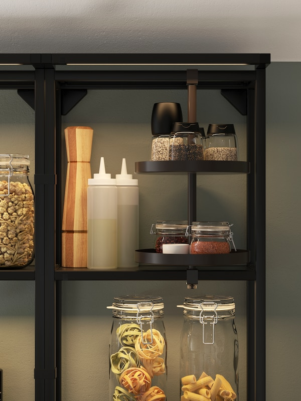 Černá otevřená police s integrovaným osvětlením a otočnou poličkou, na níž jsou skleněné nádoby s těstovinami, mlýnky na koření a ochucovadla.