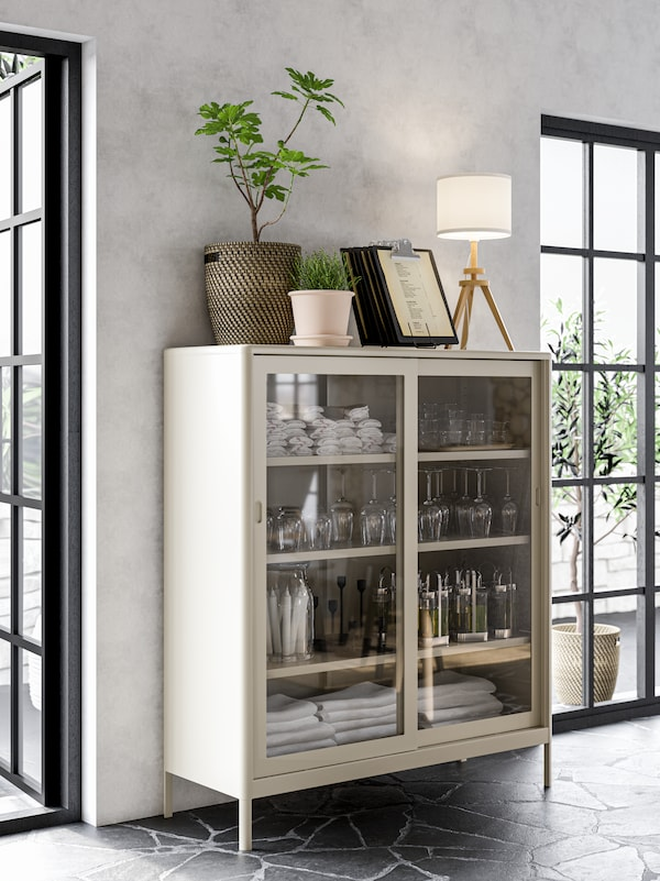 A beige cabinet with sliding glass doors with napkins, glasses and candles stored neatly in it.