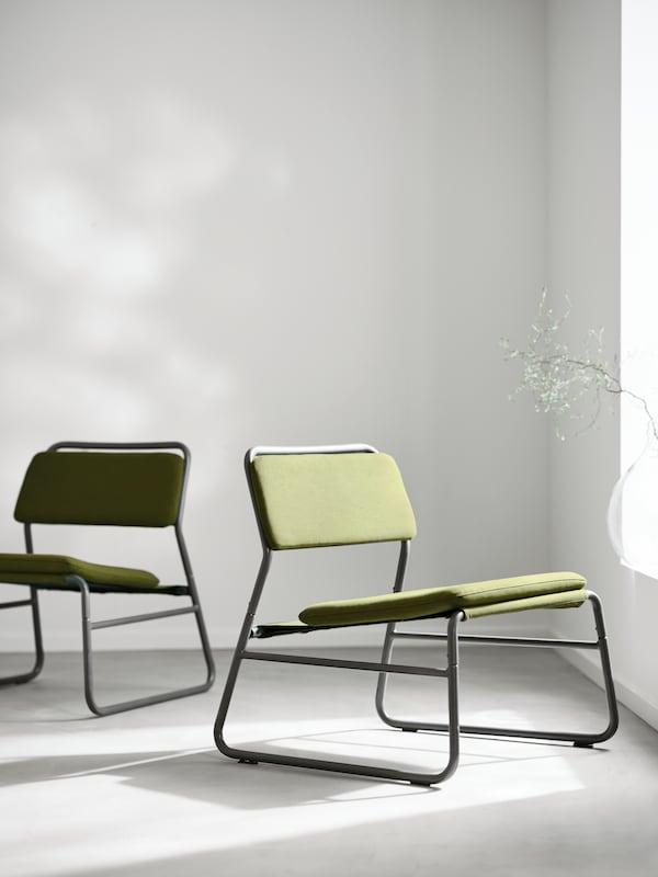 Dva LINNEBÄCK stola s črnim kovinskim ogrodjem in Orrsta olivno zelenimi prevlekami, ki sta usmerjena v nasprotno smer.