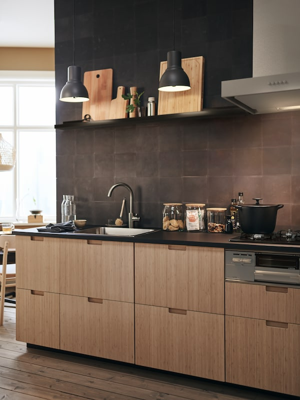 In this modern kitchen, FRÖJERED kitchen fronts in bamboo are paired with black tiled walls and accessories.