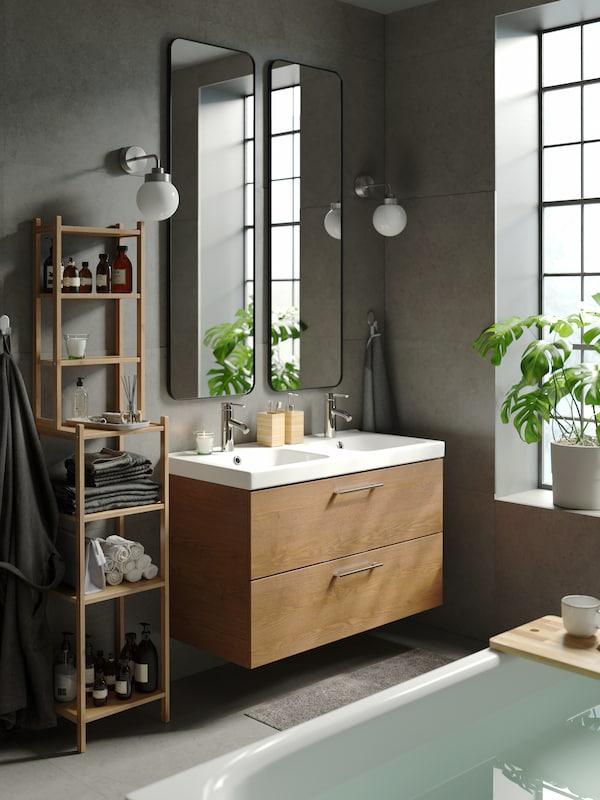 Une salle de bains contemporaine avec des murs gris. Deux miroirs LINDBYN sont installés au-dessus d'un meuble pour lavabo GODMORGON doté de deux lavabos et de deux tiroirs.