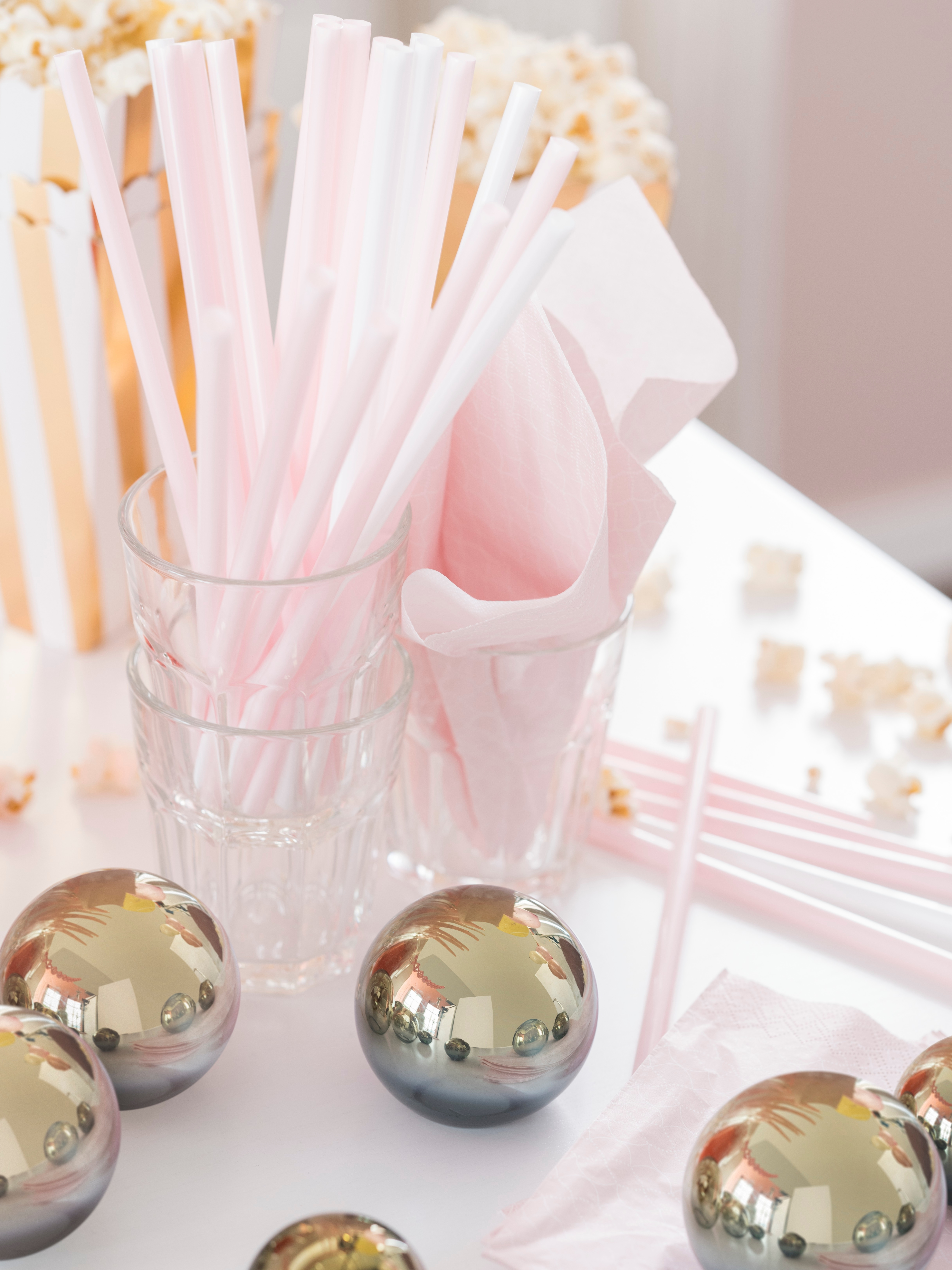 A POKAL clear glass holds reusable drinking straws by brass-coloured decoration balls and containers of popcorn on a table.