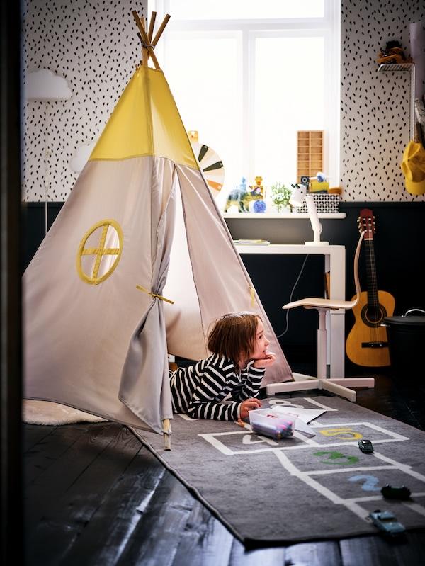 Ein kleines Kind hält sein PEKHULT Stoffspielzeug mit LED-Nachtlicht in seinem Arm. Es sitzt in einem Zelt aus rosafarbenen Decken, u. a. mit MJUKHET Stoffspielzeug.
