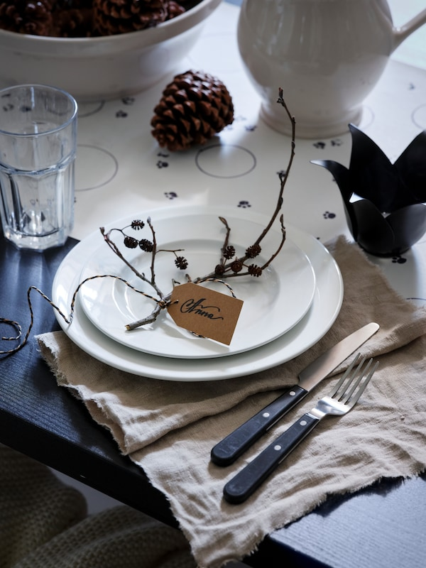 A table place setting with a white serviette and a white plate with a side plate on top, and a name tag on a twig.