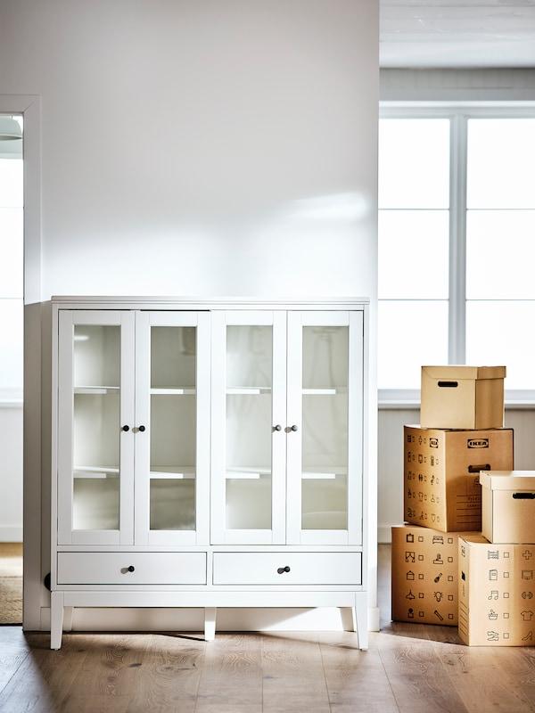 Une pièce dotée de murs blancs et d'un plancher, avec pour seul meuble une vitrine IDANÄS avec doubles portes et quelques boîtes.
