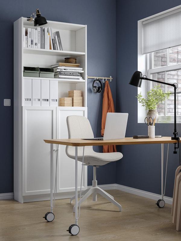 Un spațiu de lucru de acasă cu pereți de culoare albastru închis, un birou ANFALLARE/KRILLE, un scaun de conferință LÅNGFJÄLL și o bibliotecă BILLY.