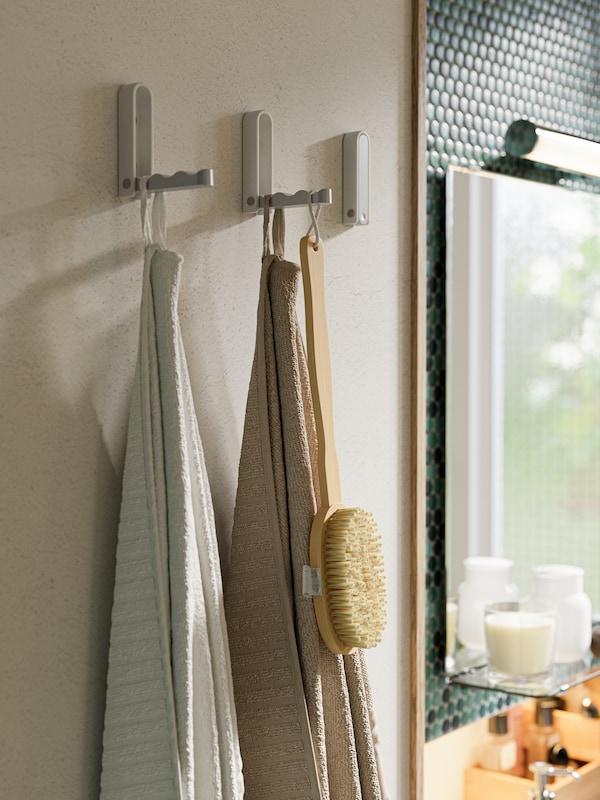 Three folding hooks on a wall, a light beige bath towel, a white bath towel and a wooden shower brush.