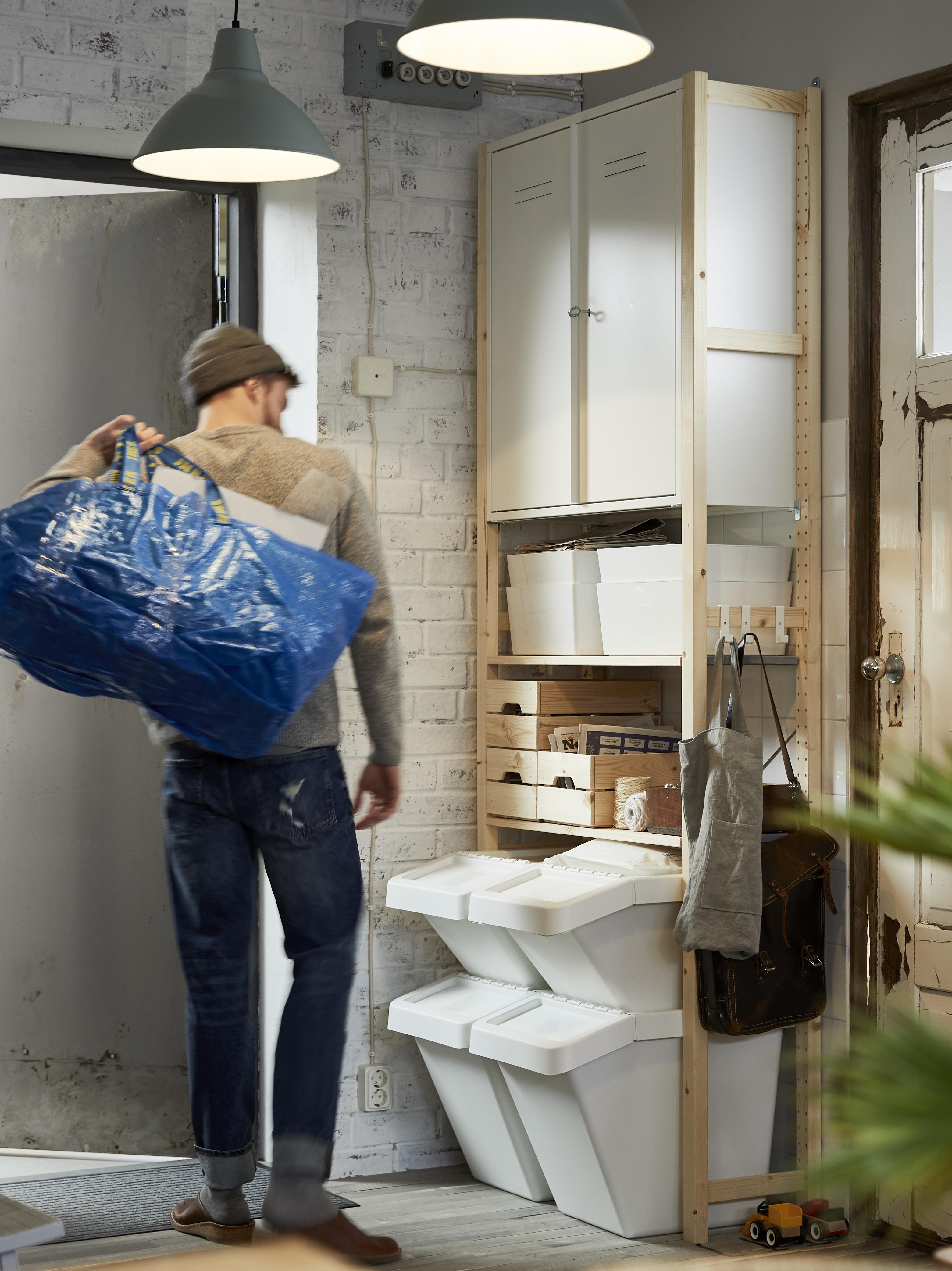 Čovjek nosi FRAKTA vreću izlazeći iz garaže u kojoj su regali, police i element za odlaganje te biljke.