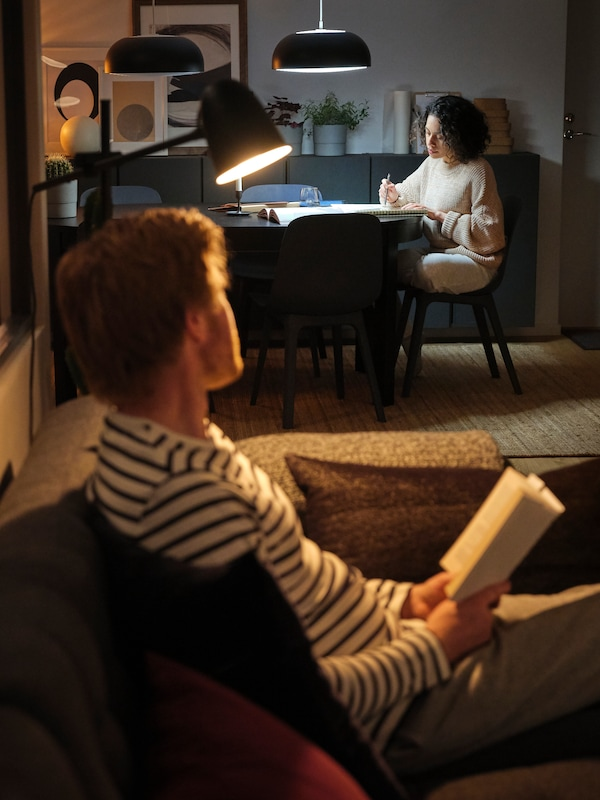 A young man sitting in a sofa looking across a room and a young woman who is sitting at a table under a hanging light.