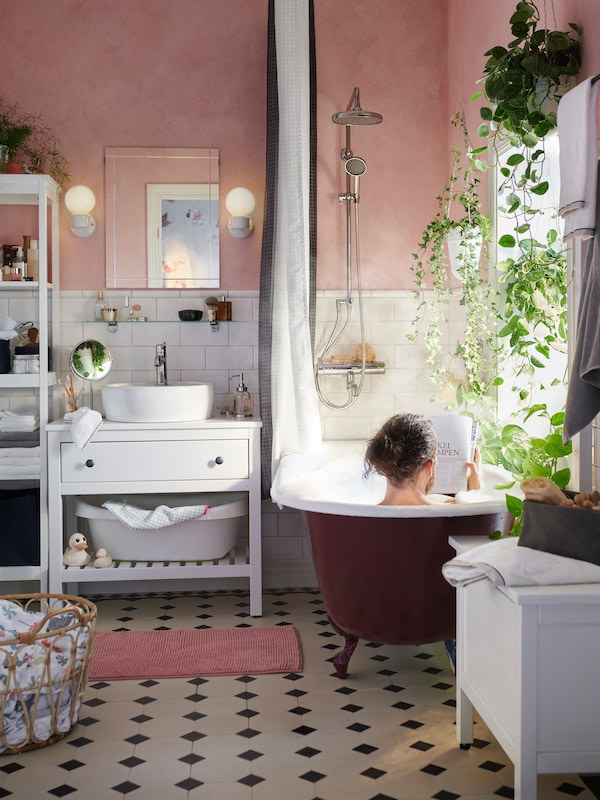 A bathroom in traditional style with a HEMNES washstand, pink walls and plants. A man is in a bathtub reading a magazine.