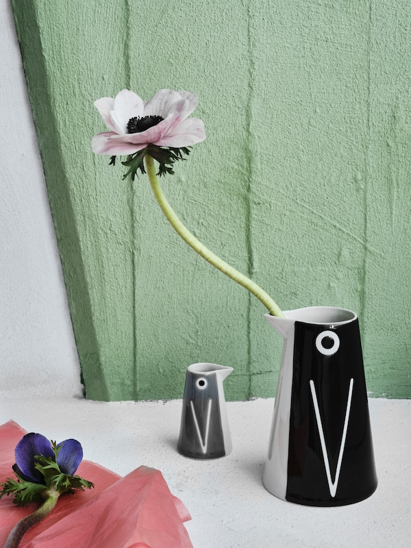 One large, black-white LÄTTSÅLD vase with an artificial flower and one small grey-white vase, both with penguin designs.