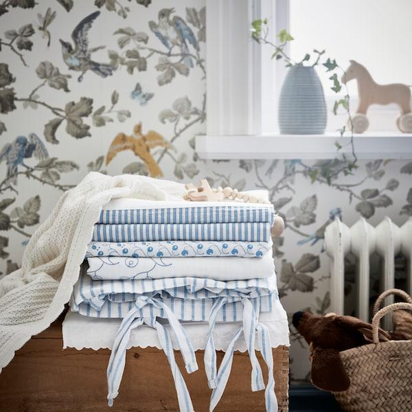 Morea de téxtiles enriba dunha caixa de madeira nun cuarto infantil cunha funda nórdica e unha funda de almofada GULSPARV, xunto con cortinas GULSPARV.