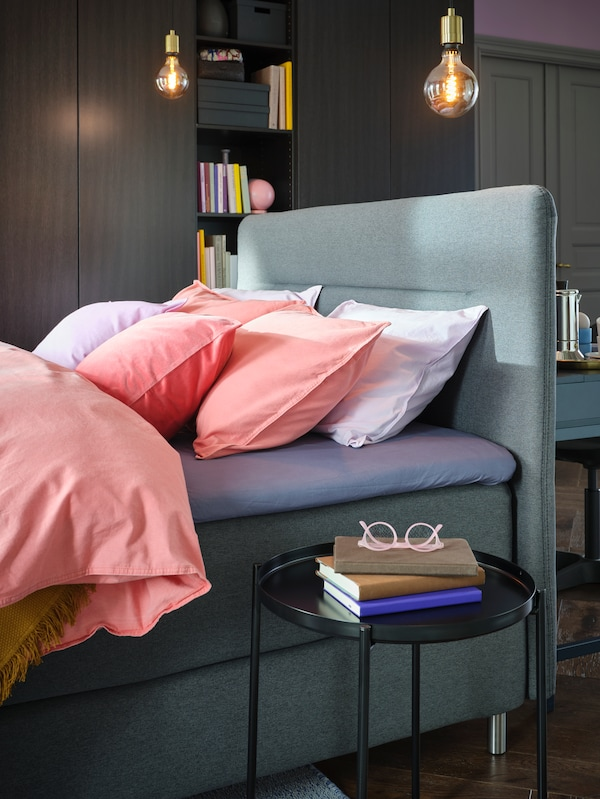 Part of a bedroom with the head of a FINNSNES divan bed with colourful bed linen, and a GLADOM tray table beside the bed.