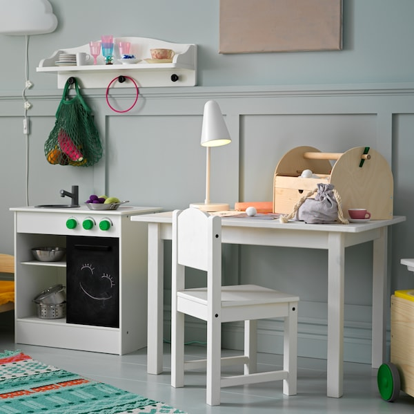 A NYBAKAD play kitchen with a SOLGUL wall shelf above it, next to a white SUNDVIK children's table and children's chair.