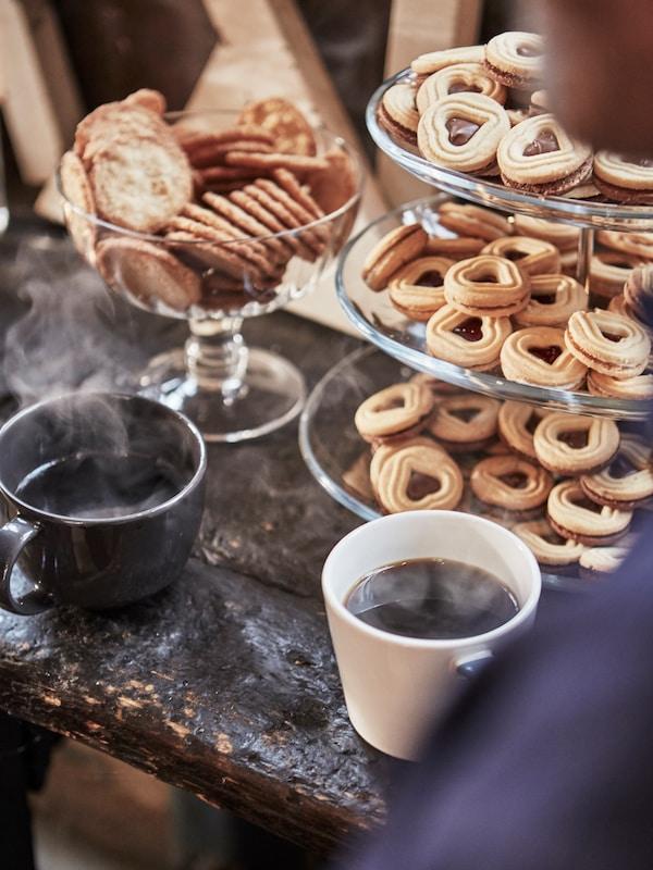 쿠키가 가득 채워진 3단 서빙 트레이 주변에 김이 나는 커피가 담긴 머그컵이 놓여져 있는 모습.