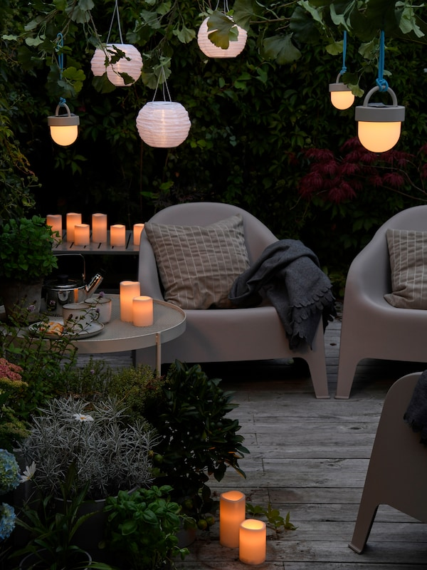 Seating group on a patio in waning daylight, lit up by GODAFTON LED block candles and hanging solar-powered LED lamps.