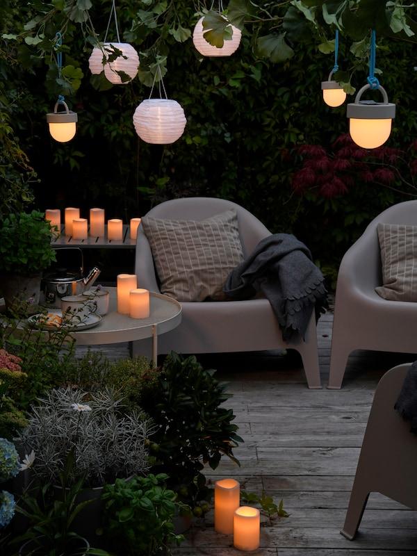 Talde bat dago patio batean eserita; egun-argia gutxiagotzen doa eta GODAFTON LED kandela lodiek eta zintzilik dauden eguzki-energiaz funtzionatzen duten LED lanparek argitzen dute espazioa.
