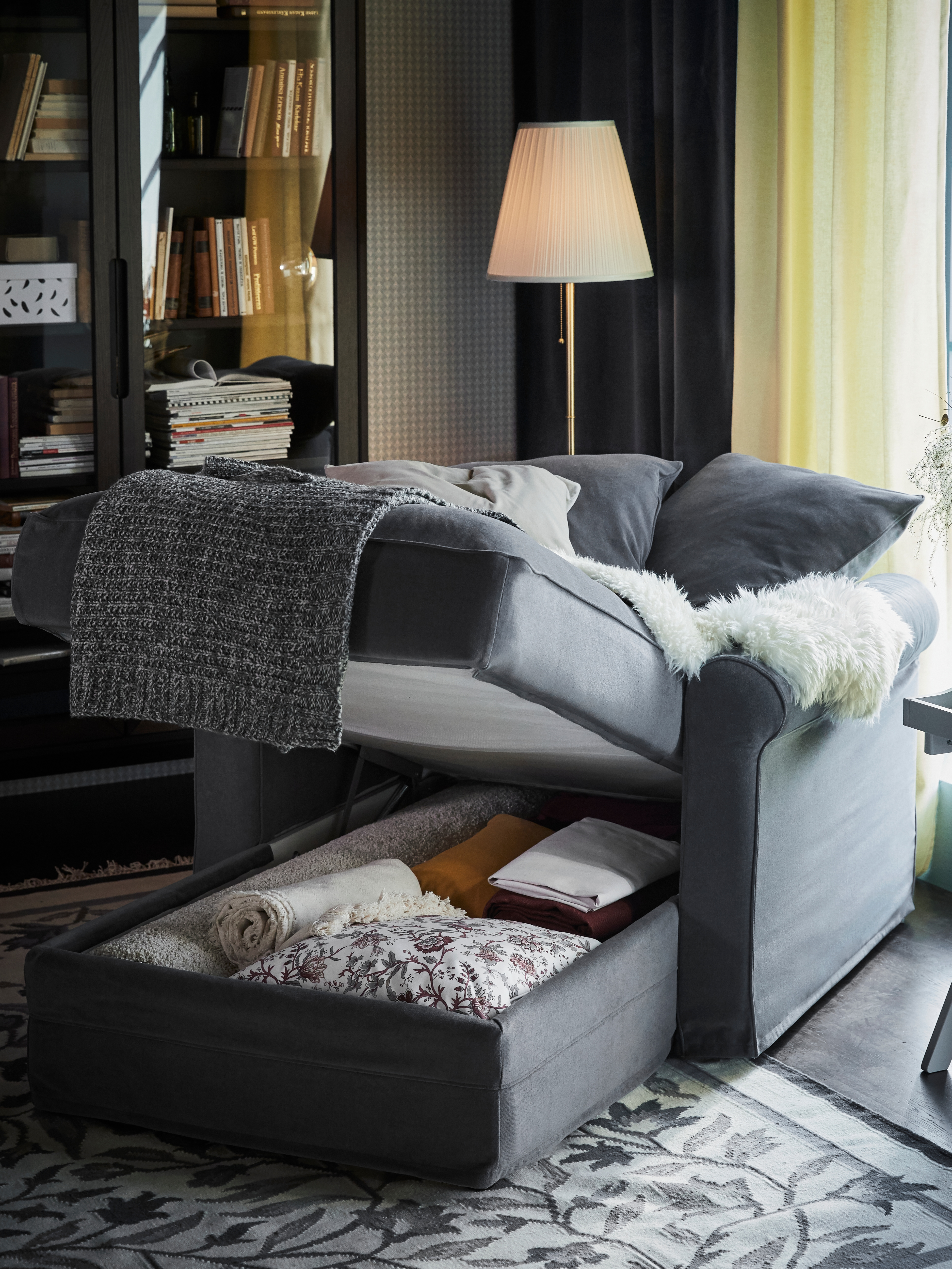 A Ljungen medium grey GRÖNLID chaise longue is by a cabinet. Its seat is lifted to show storage of cushions and throws.