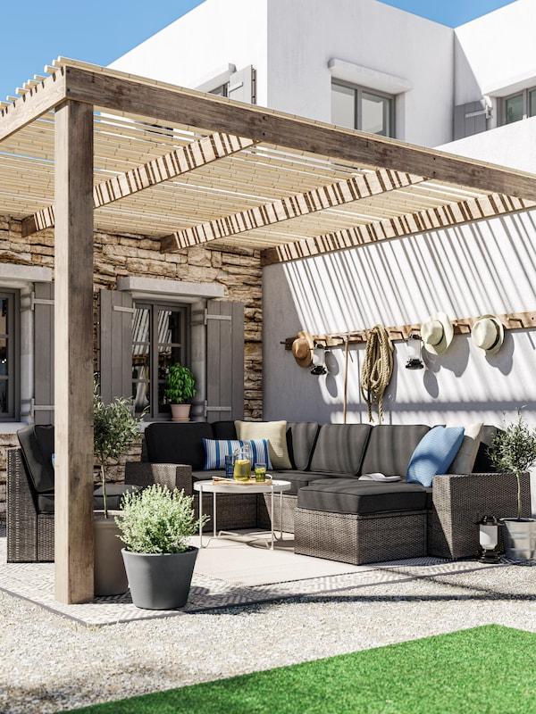 Ein Loungebereich mit einem dunkelgrauen Outdoor-Sofa, anthrazitfarbenen Kissen, einem beigefarbenen Couchtisch, passendem Bodenrost und Topfpflanzen.