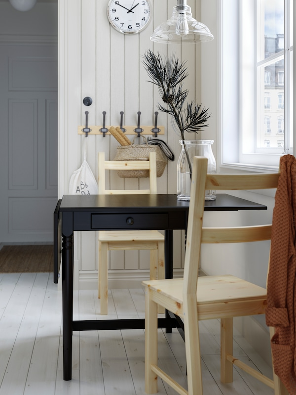A black drop-leaf table with drawer, two pine chairs, a wooden rack with hooks, a wall clock and a glass pendant lamp.