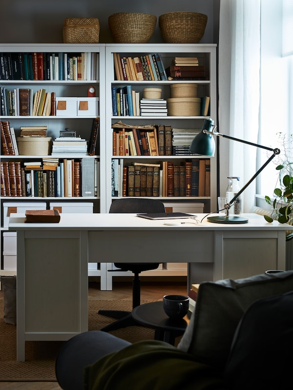 A room with bookcases full of books, baskets on top, and other diverse items, a grey desk with white work top and chairs.