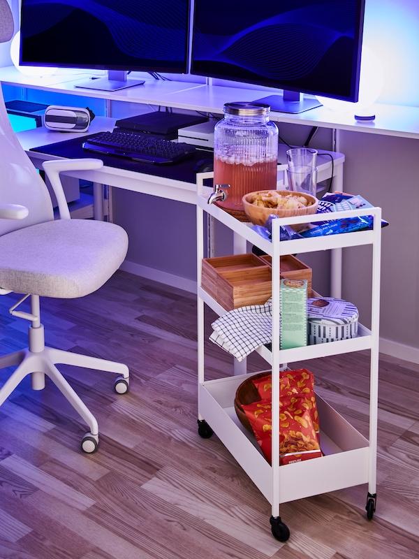軽食やレモネードを置いたホワイトのキャスター付きワゴンが、オフィスチェアと、パソコンモニター2台を置いた棚の脇にある。