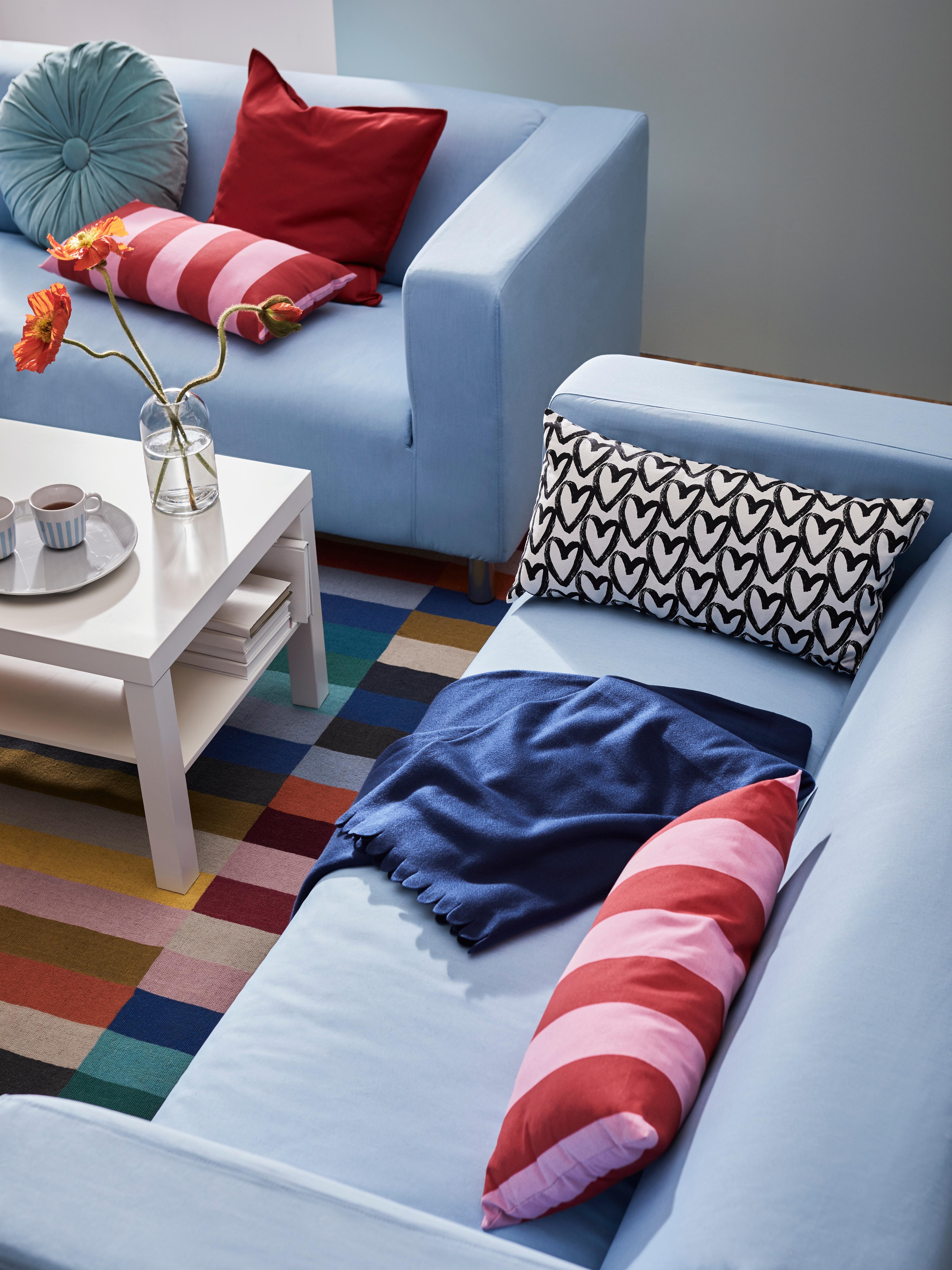 Dvije blijedoplave sofe sa stolićem za kavu i višebojnim tepihom, plava POLARVIDE lagana deka, šareni ukrasni jastuci i cvijeće u vazi.