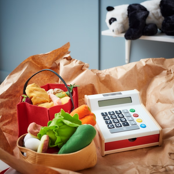 A toy cash register and plush vegetables, with a stuffed panda in the background.