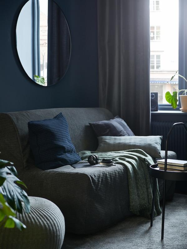Le coin d'une pièce avec un canapé-lit deux places LYCKSELELÖVÅS, une table d'appoint BURVIK noire et un miroir LINDBYN.