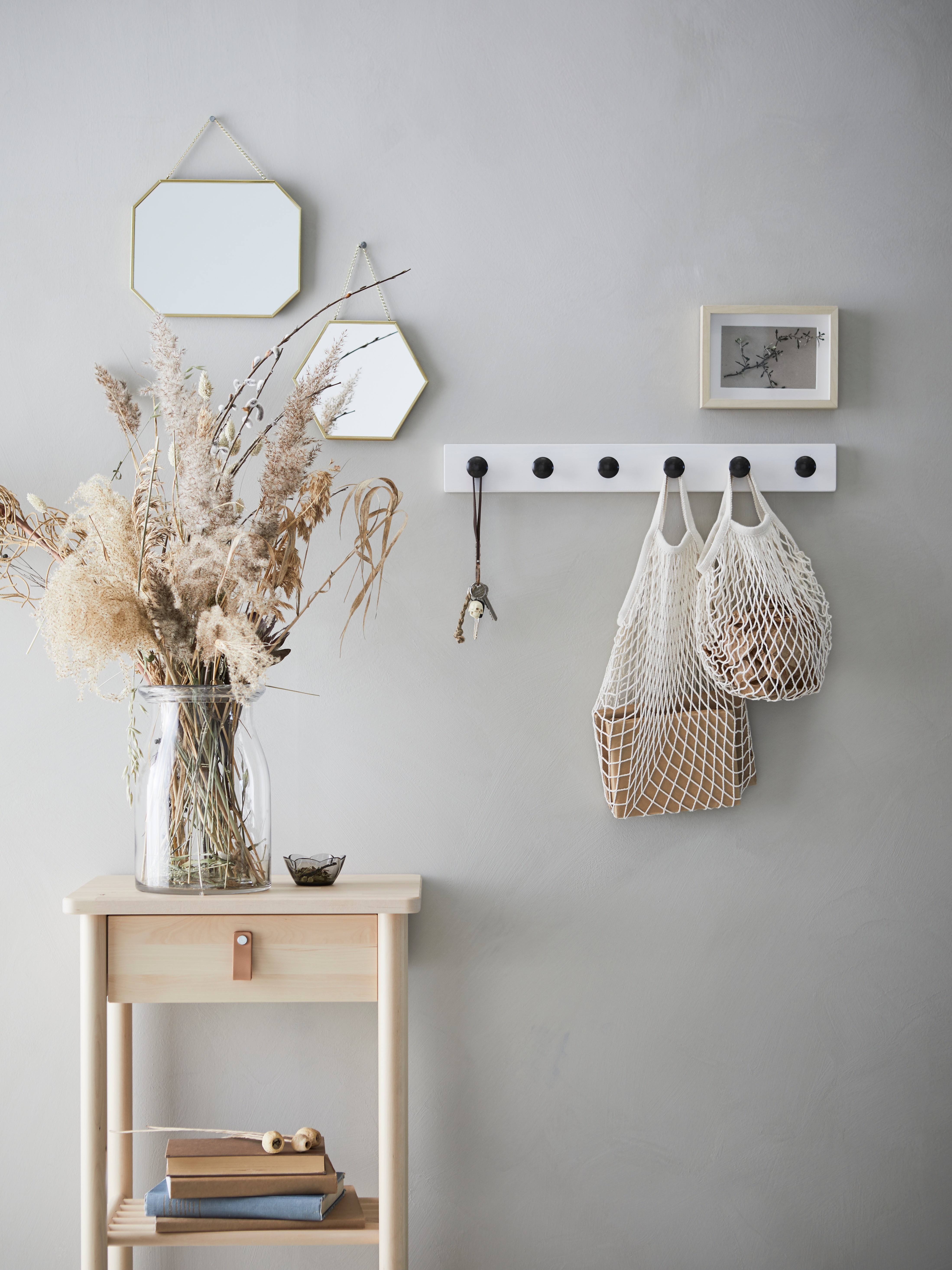 A wall with LASSBYN mirrors, a picture frame and net bags on a hook rail behind side table with vase of dried flowers.