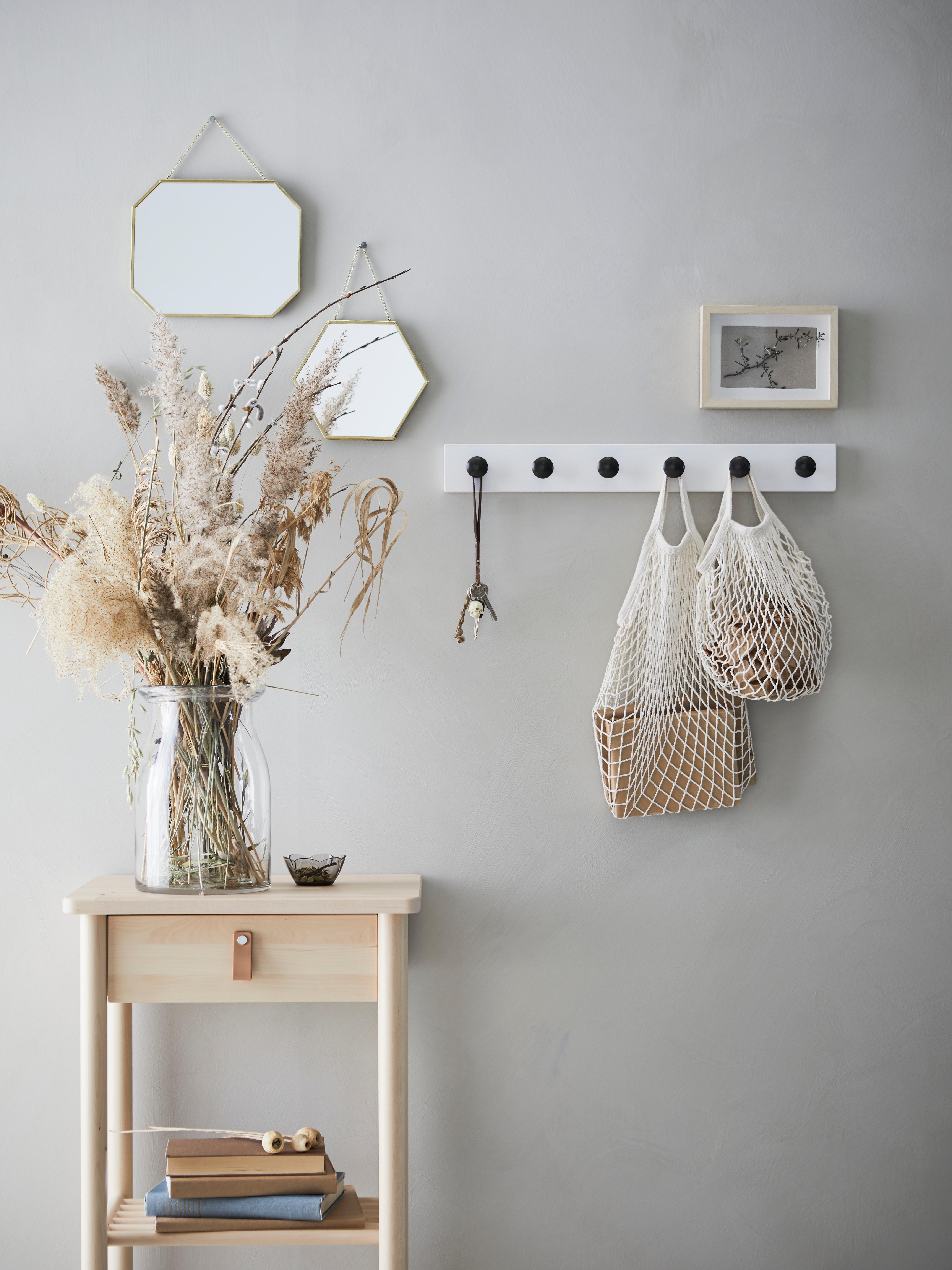 LASSBYN 라스뷘 거울과 액자, 네트가방이 후크 레일에 걸려 있는 벽 앞의 보조테이블에 말린꽃을 꽂은 꽃병이 놓여 있어요.