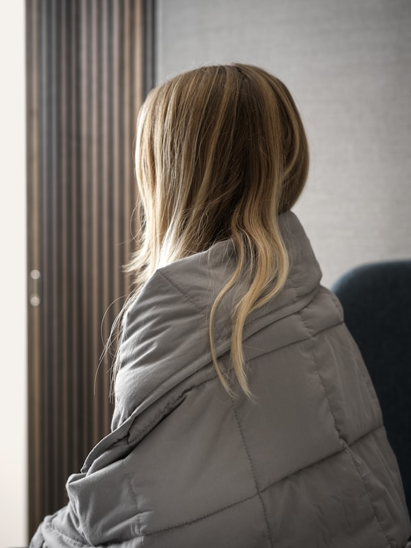 A woman sitting in a warm grey room holding a dark grey ODONVIDE weighted blanket around her and looking towards a window.